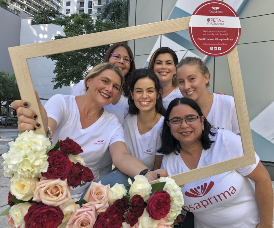 Rosaprima Miami team poses with a floral frame made by them for Petal It Forward 2019