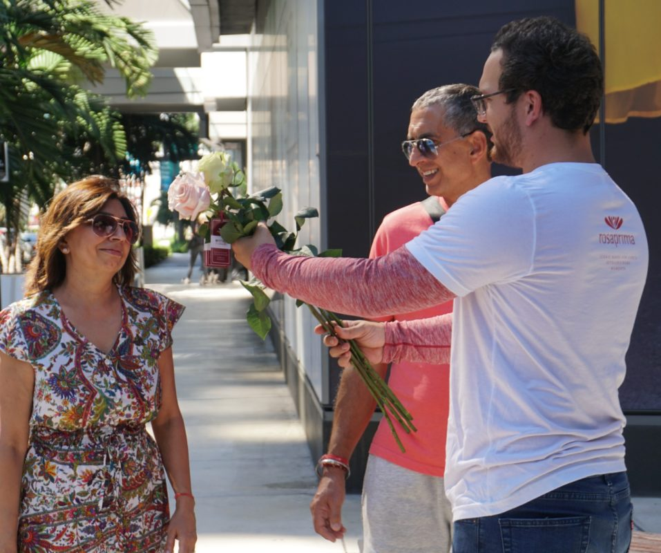 A woman walking with her husband receives two Rosaprima roses as part of the Petal It Forward 2019 campaign.